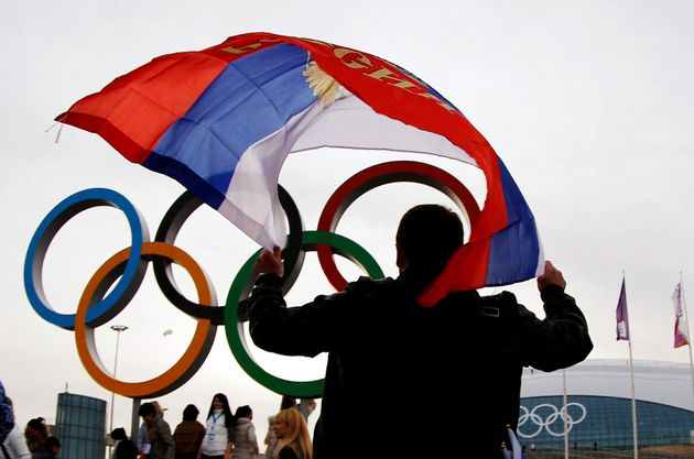 FILE PHOTO: A man carries the Russian flag past the Olympic rings at the Olympic Park during the 2014...