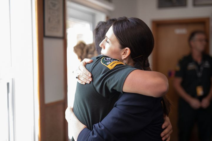 New Zealand Prime Minister Jacinda Ardern hugs a first responder who helped those injured in the White Island volcano eruptio