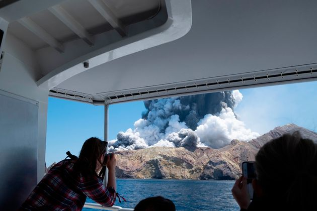 In this Dec. 9, 2019, photo provided by Michael Schade, tourists on a bout film the eruption of the volcano...