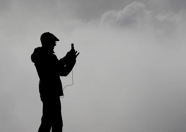 Una persona toma una fotografía en el alto de El Perdón, de la espesa niebla que cubría la comarca de