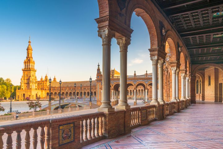 Sunrise on the old tower seen from colonnade of the semi-circular portico, Plaza de Espana, Seville, Andalusia, Spain