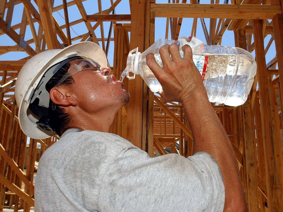 A construction worker drinks a bottle of water while working on a site in Rancho Cordova, California.