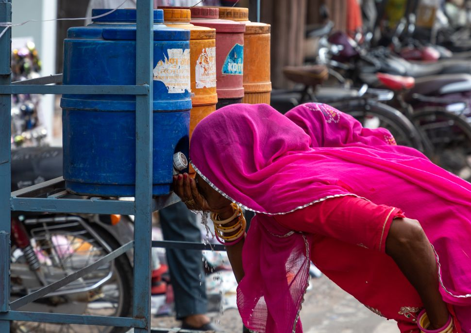 Women drinking water in the street during the heat wave in Bikaner, Rajasthan, India on July 25, 2019. Temperatures in the st