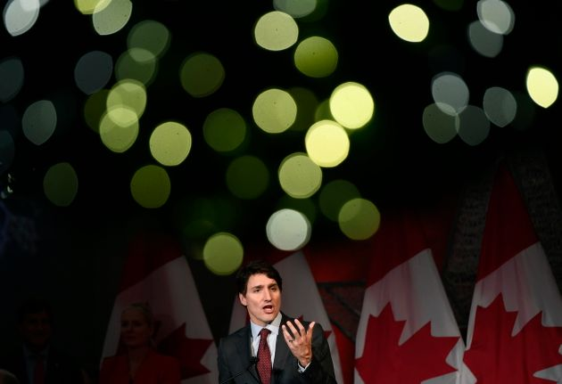Christmas lights on a wreath glow above Prime Minister Justin Trudeau as he speaks to supporters at the...