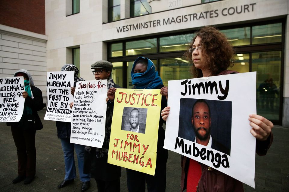 Supporters of Jimmy Mubenga's family pose with placards outside Westminster Magistrates