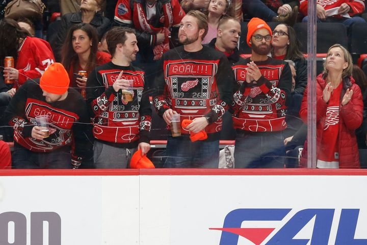 Detroit fans wearing matching Red Wing-themed ugly Christmas sweaters at a game on Dec. 22, 2018.