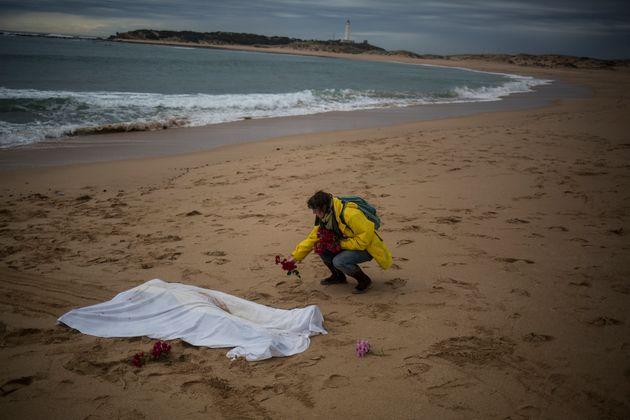 Kate Abrahams, una mujer belga, pone flores junto al cuerpo de un migrante ahogado en la playa de Caños...