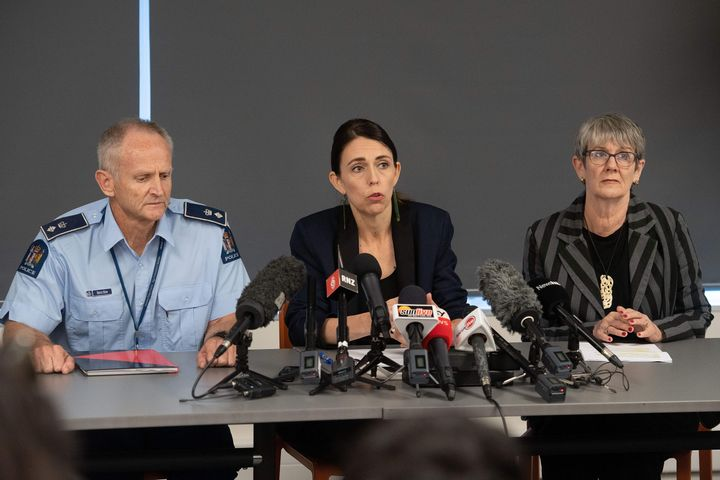 """Prime Minister of New Zealand Jacinda Ardern (C) with New Zealand Police Superintendent Bruce Bird (L) and Whakatane Mayor Judy Turner (R) speak to the media about the eruption of Whakaari/White Island during a press conference in Whakatane on December 10, 2019. - New Zealand's Prime Minister Jacinda Ardern expressed """"unfathomable grief"""" on December 10 after a volcanic eruption on a popular tourist island that is thought to have claimed 13 lives. (Photo by Marty MELVILLE / AFP) (Photo by MARTY MELVILLE/AFP via Getty Images)"""