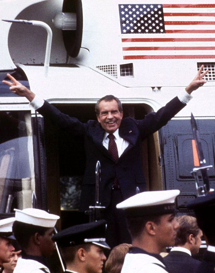 Following his resignation, U.S. President Richard M. Nixon flashes the V-for-victory sign as he boards his Marine One helicop