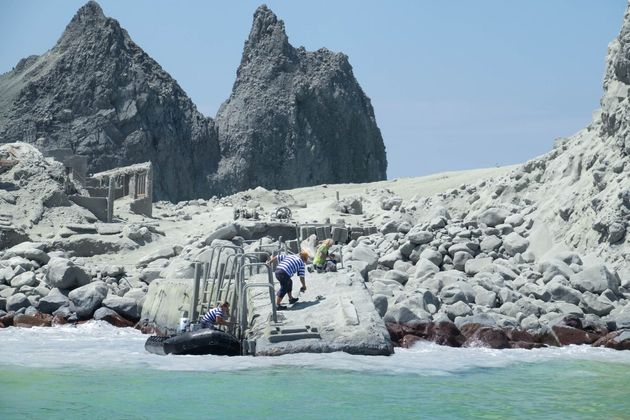 Tour guides evacuate tourists on a boat shortly after the volcano eruption on White Island, New Zealand...