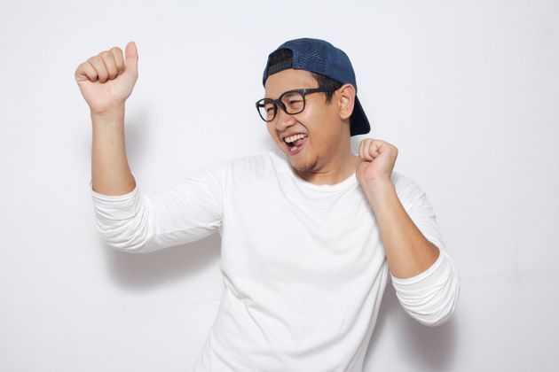 Photo image closeup portrait of a funny young Asian man dancing happily joyful expressing celebrating...