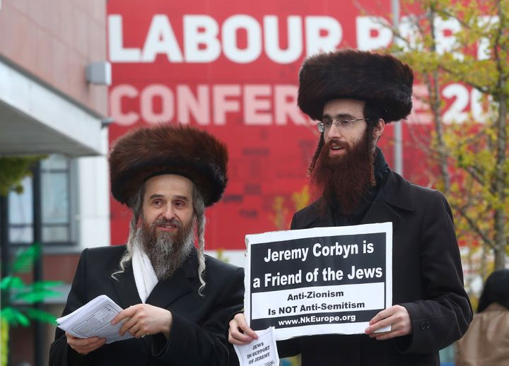 Two men wearing Orthodox Jewish attire hold placards and leaflets in support of Labour Party leader Jeremy Corbyn outside the