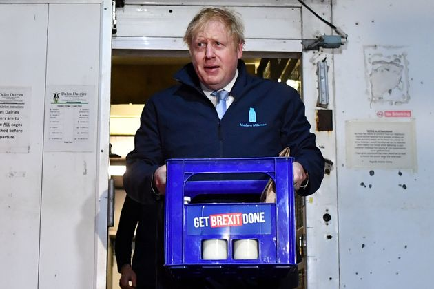 Boris Johnson carries a crate of milk while campaigning for the general