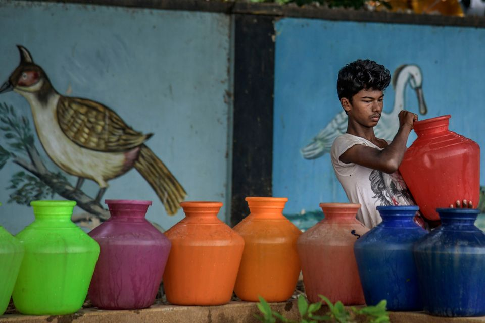 A boy carries water cans being filled at the Metro water filling station in the heart of Chennai on June...