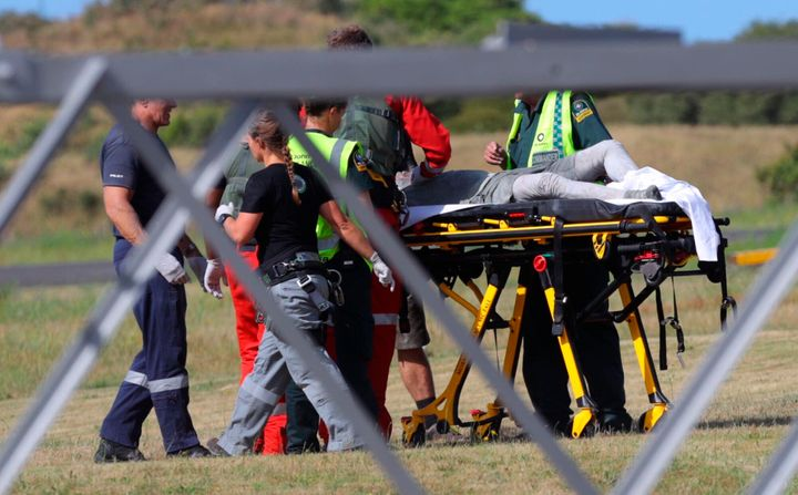 Emergency services attend to an injured person arriving at the Whakatane Airfield after the volcanic eruption on Monday.