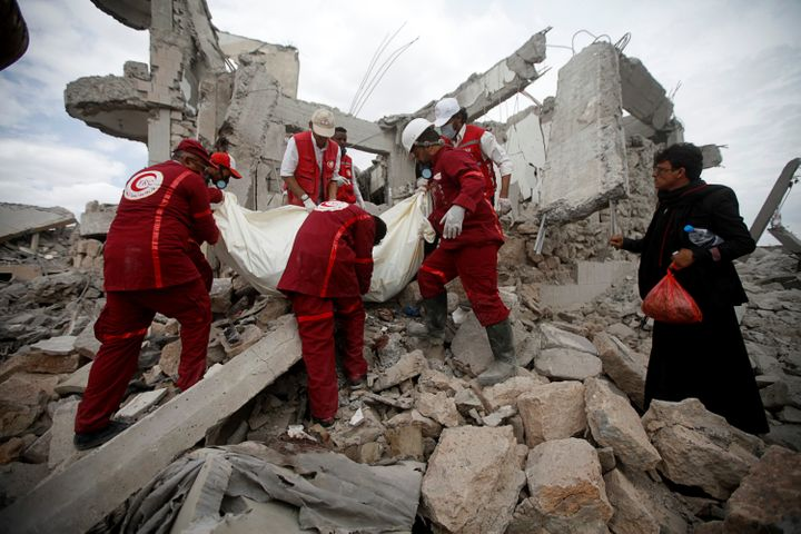 Red Crescent medics remove the body of a victim of Saudi-led airstrikes on a Houthi detention center in Dhamar, Yemen, on Sep