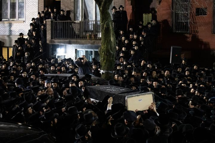Orthodox Jewish men carry Moshe Deutsch's casket outside a Brooklyn synagogue following his funeral, Wednesday, Dec. 11, 2019