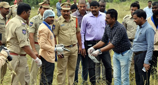 A forensic official ((3L) holds a gun as police officers gather around the body of man at the site where...
