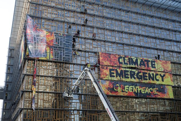 Un grupo de bomberos desaloja a los activistas de Greenpeace, esta mañana, en el Edificio Europa...