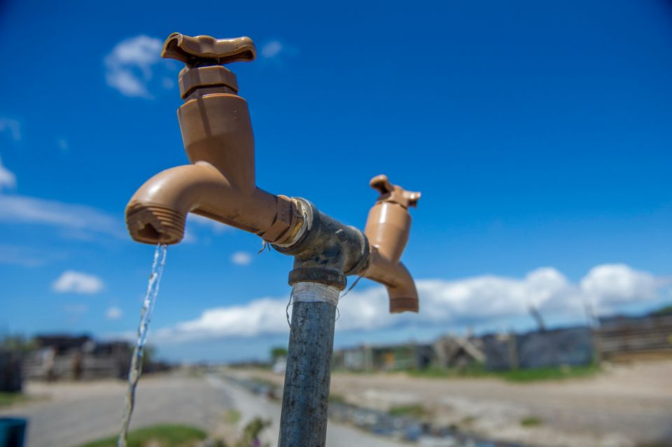 A communal tap runs for people in an informal settlement near Cape Town, South Africa, in January 2018....
