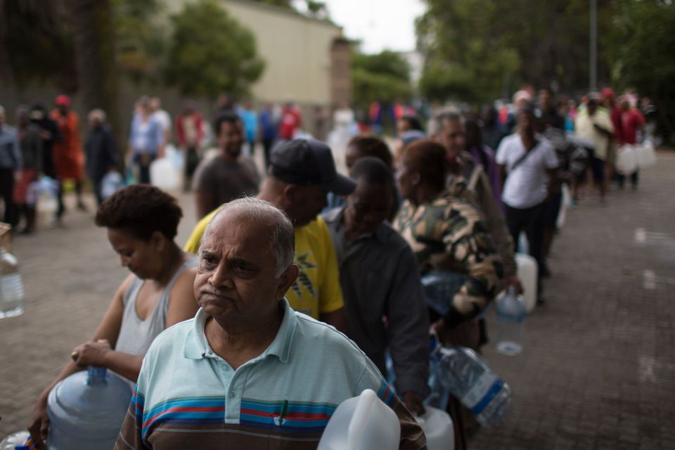 Residents wait to fill containers with water at a natural spring water source in Cape Town in February...