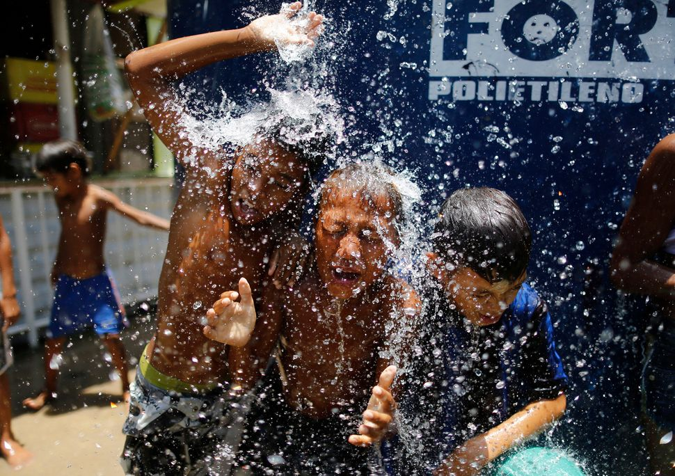Children play under the water from a water tank at the Alemao Complex neighborhood in Rio de Janeiro in January 2015. Accordi
