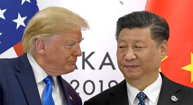 FILE - In this June 29, 2019, file photo, U.S. President Donald Trump, left, shakes hands with Chinese...