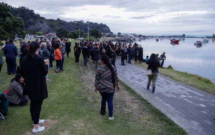 Locals sing during sunrise as they wait for the return of the victims after the White Island eruption to be returned to Whaka