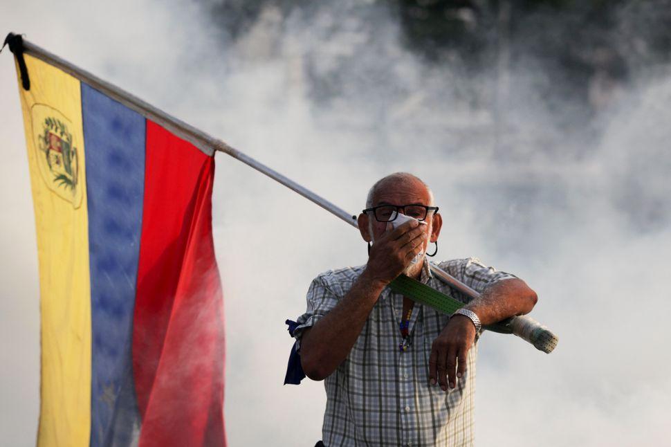 Un oponente de Maduro con una bandera venezolana se cubre la cara contra el gas lacrimógeno disparado durante un intento de levantamiento militar