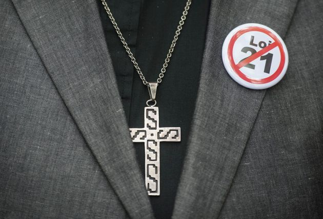 A button denouncing Bill 21 is shown on a lapel next to a crucifix during a demonstration against the...