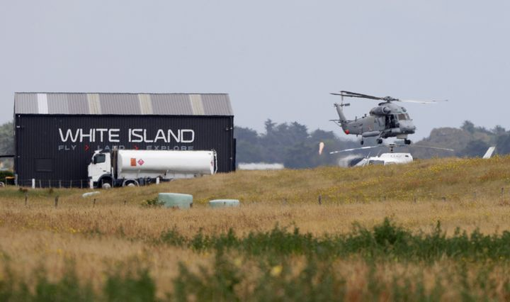 A Navy helicopter hovers at Whakatane Airport, as the recovery operation to return the victims of the Dec. 9 volcano eruption continues off the coast of Whakatane New Zealand, Friday, Dec. 13, 2019. A team of eight New Zealand military specialists landed on White Island early Friday to retrieve the bodies of victims after the Dec. 9 eruption. (AP Photo/Mark Baker)