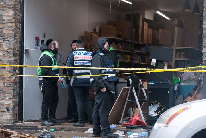 Emergency personnel and investigators work at the scene the day after an hours-long gun battle with two men around a kosher m