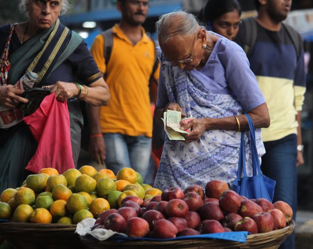 An old woman buys fruits from a roadside stall in Mumbai on 14 November