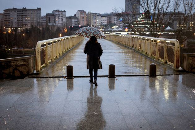 Una mujer se protege de la lluvia con un paraguas mientras pasea por las calles de