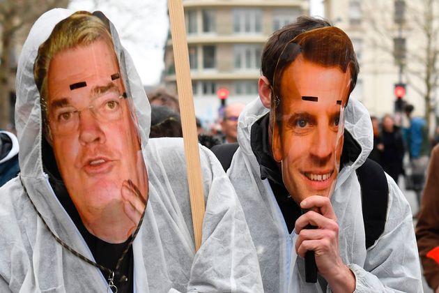 Des manifestants portent des masques représentant le président Emmanuel Macron et le haut-commissaire...