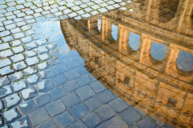 Coliseum reflected in a puddle and cobblestones. Roma