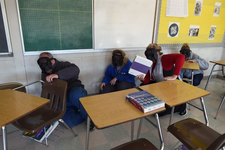"Participants hide from an ""active shooter"" during ALICE training at the Harry S Truman High School in Levittown, Pennsylvania"