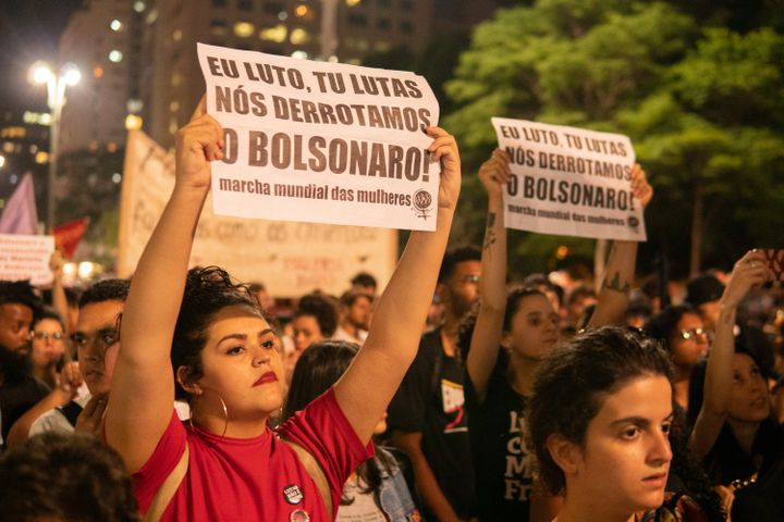 "A woman holds a paper that reads ""I fight, you fight, we defeat Bolsonaro!"" during a protest in São Paulo, Brazil, Oct"