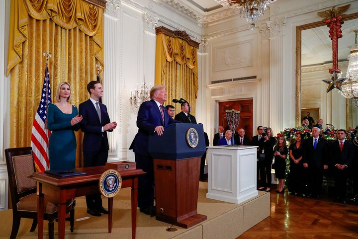 President Donald Trump is applauded by White House senior advisors Ivanka Trump and Jared Kushner prior to signing an executi