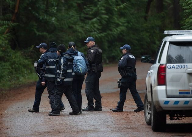 RCMP officers and members from the coroner's office walk into the dense woods near the scene of a small...