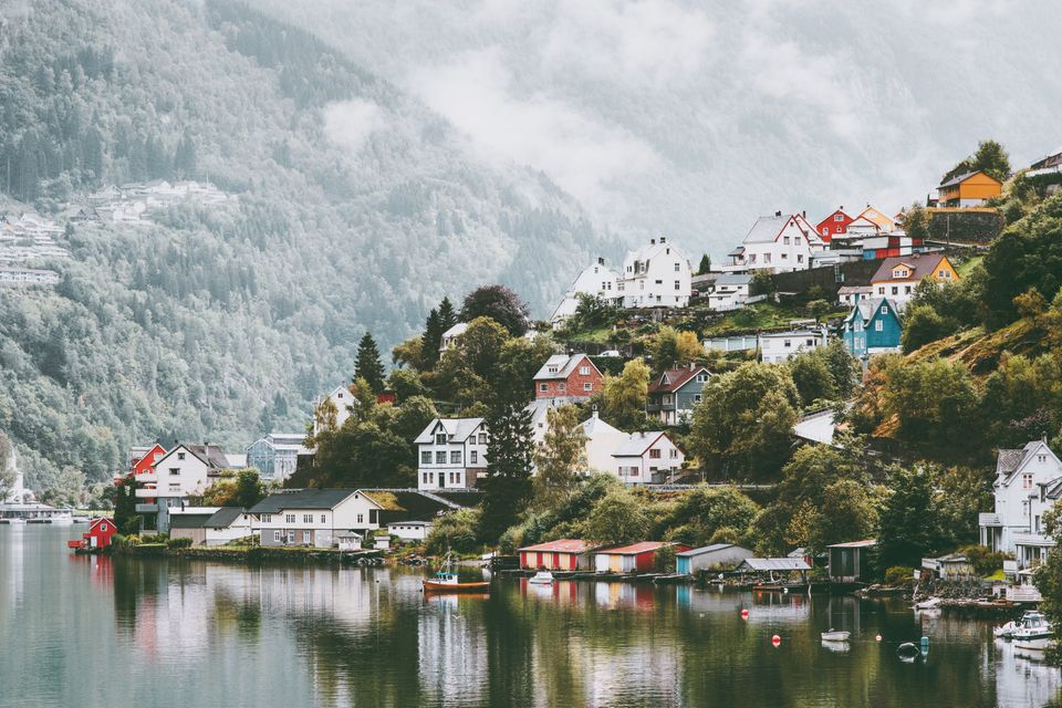 Odda city houses in Norway Landscape foggy mountains and water reflection
