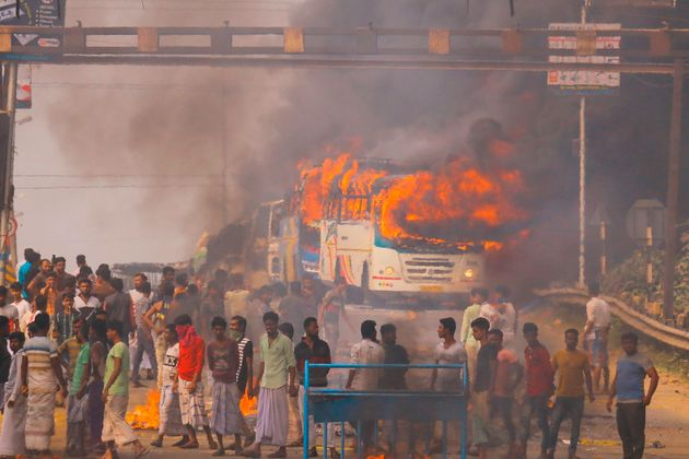 Protesters block a road after setting buses on fire during a demonstration against the Citizenship Act...