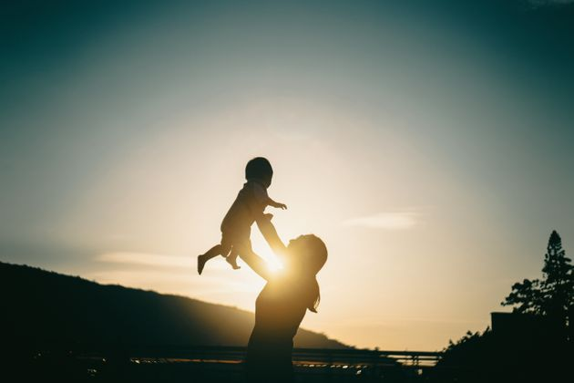 Silhouette of mother raising baby girl in the air outdoors against sky during a beautiful