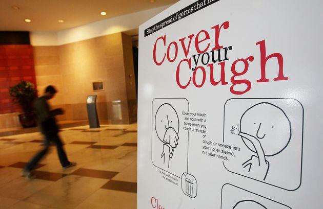アメリカのニューヨーク市内で貼られた政府によるポスター。「咳は飛ばさず、ティッシュや肘で覆おう」と書かれている=ニューヨーク、2009年9月