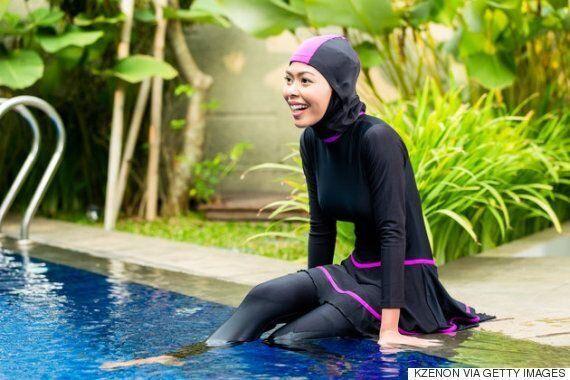 ブルキニ姿で水泳プールでくつろぐイスラム教徒の女性