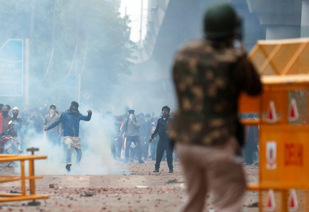 A protestor kicks a tear gas shell during a protest against the Citizenship Amendment Bill, a bill that...