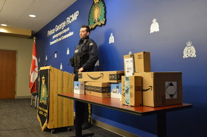 Cst. Brent Benbow stands next to Amazon packaging as he speaks to media in Prince George, B.C.