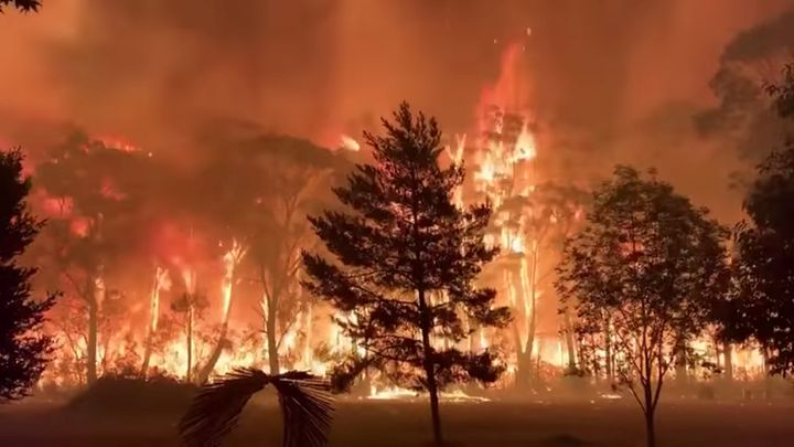 A fire blazes across bush as seen from Mount Tomah in New South Wales, Australia December 15, 2019 in this still image obtained from social media video. NSW RFS