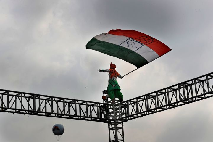 An opposition Congress party worker waves party flag standing atop a steel scaffolding at a rally organized by party to prote