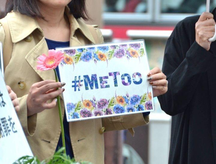 花を手にするフラワーデモの参加者=11月18日、長崎市
